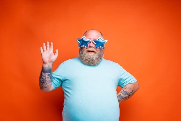 Homem gordo e feliz com tatuagens de barba e óculos de sol fazendo um gesto de olá com a mão