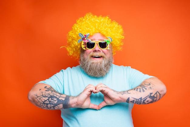 Homem gordo e feliz com tatuagens de barba e óculos de sol moldando o coração com as mãos