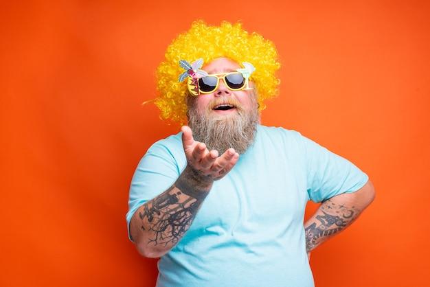 Homem gordo e feliz com tatuagens de barba e óculos escuros se diverte com a peruca amarela