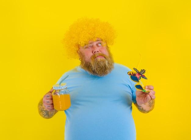 Homem gordo e pensativo com peruca na cabeça e óculos escuros bebe um suco de fruta