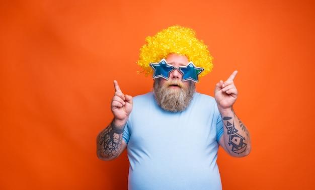 Homem gordo e pensativo com tatuagens de barba e óculos de sol dançando música em uma discoteca