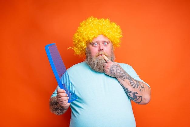 Homem gordo e pensativo com tatuagens de barba e óculos de sol se penteando com um pente gigante