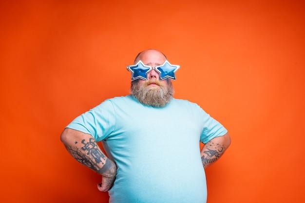 Homem gordo e pensativo com tatuagens de barba e óculos escuros não tem certeza de algo