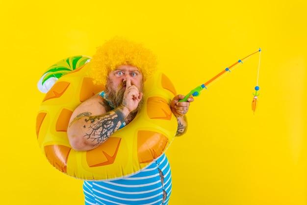 Homem gordo e sério com peruca na cabeça brincando com a vara de pescar