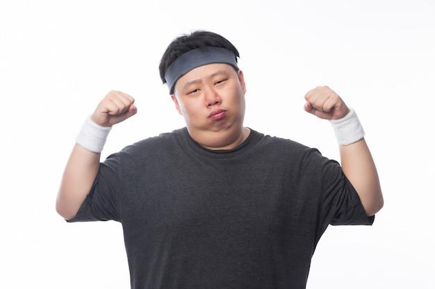 Homem gordo engraçado asiático em roupas esportivas, mostrando a força
