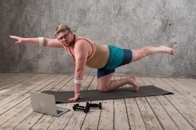 Homem gordo engraçado em roupas esportivas, fazendo exercícios. ele pratica esportes remotamente enquanto olha para seu laptop.