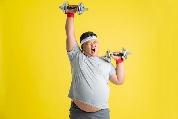 Homem gordo está exercitando, levantando pesos