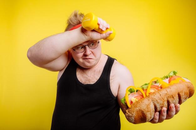 Homem gordo fatigado transpira enquanto levanta hambúrguer