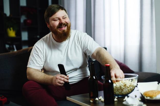 Homem gordo feliz se senta no sofá e assiste tv com pipoca e cerveja