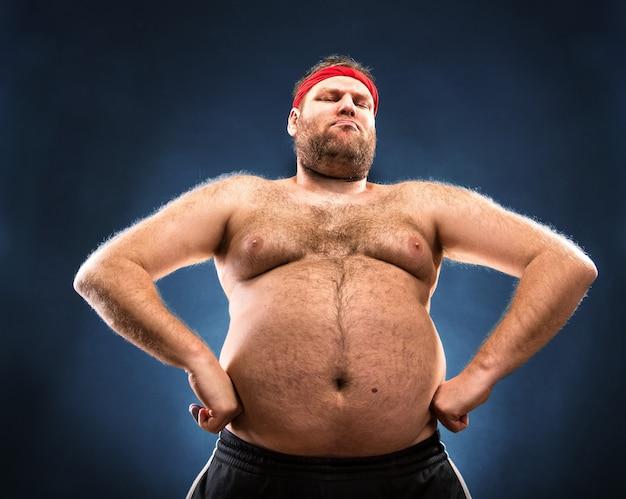 Homem gordo imitando construção muscular. visão de baixo ângulo Foto Premium