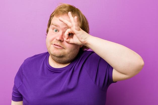 Homem gordo jovem ruiva autêntica animado mantendo o gesto bem no olho.