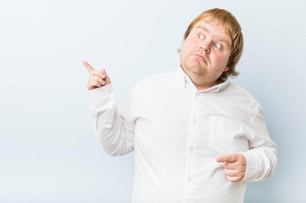 Homem gordo jovem ruiva autêntica chocado apontando com o dedo indicador para um espaço de cópia.
