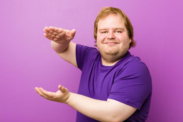 Homem gordo jovem ruiva autêntica chocado e espantado, segurando um espaço de cópia entre as mãos.