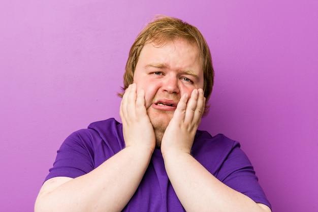 Homem gordo jovem ruiva autêntica choramingando e chorando desconsolado.