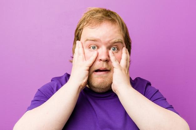 Homem gordo jovem ruiva autêntica comemorando uma vitória ou sucesso, ele fica surpreso e chocado.