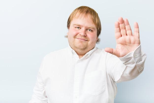 Homem gordo jovem ruiva autêntica em pé com a mão estendida, mostrando o sinal de stop, impedindo-o.