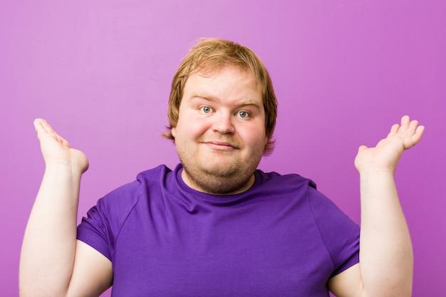 Homem gordo jovem ruiva autêntica faz escala com os braços, sente-se feliz e confiante.