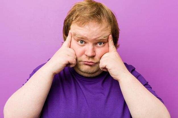 Homem gordo jovem ruiva autêntica focado em uma tarefa, mantendo os dedos apontando a cabeça.