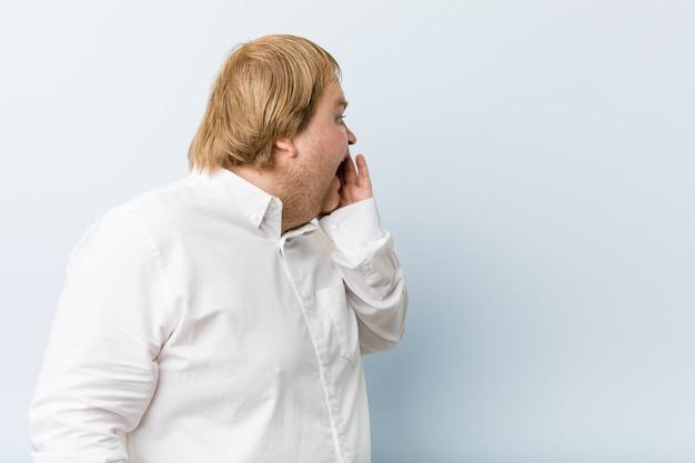 Homem gordo jovem ruiva autêntica grita alto, mantém os olhos abertos e mãos tensas.