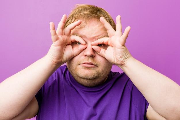 Homem gordo jovem ruiva autêntica mostrando sinal bem sobre os olhos