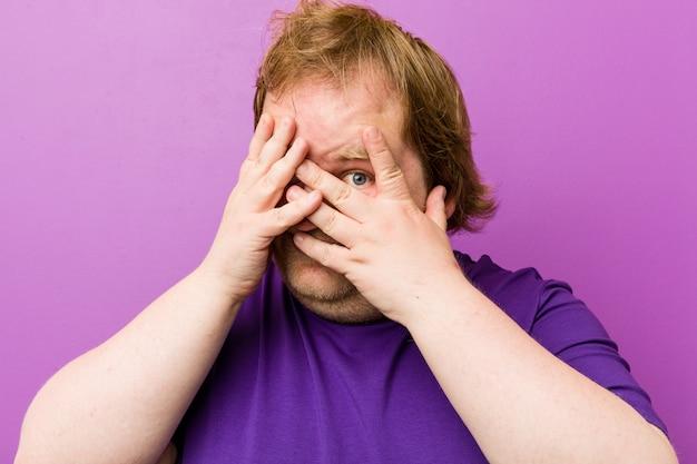 Homem gordo jovem ruiva autêntica pisca entre os dedos, assustado e nervoso.