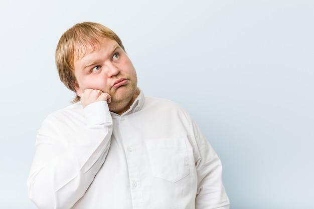 Homem gordo jovem ruiva autêntica que se sente triste e pensativo, olhando para o espaço da cópia.
