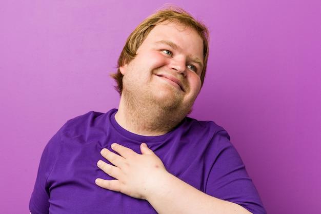 Homem gordo jovem ruiva autêntica ri alto, mantendo a mão no peito.
