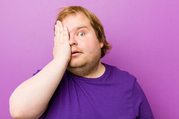 Homem gordo jovem ruiva autêntica se divertindo cobrindo metade do rosto com a palma da mão.