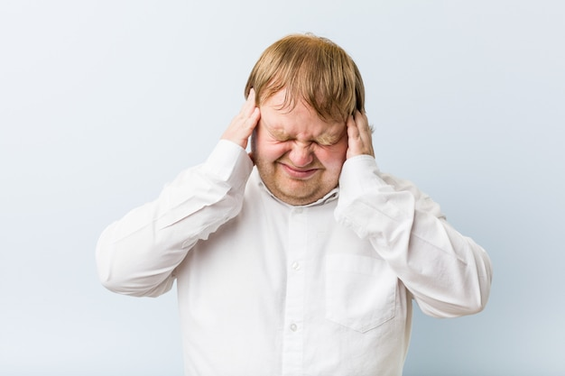 Homem gordo jovem ruiva autêntica tocando os templos e tendo dor de cabeça.