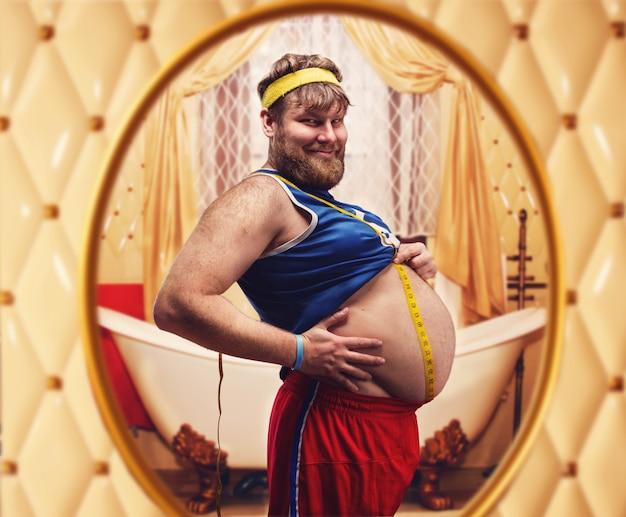 Homem gordo medindo a barriga olhando no espelho
