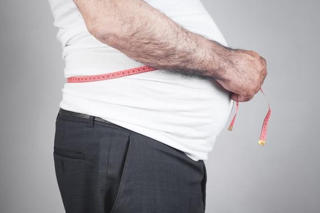 Homem gordo medindo sua barriga com fita métrica.
