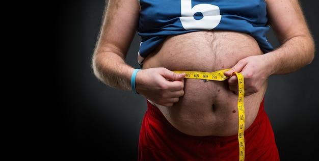 Homem gordo medindo sua grande barriga sobre cinza