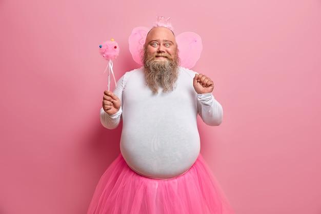 Homem gordo positivo se diverte na festa temática, parece uma fada que realiza sonhos, arrepia-se com as crianças, tem barba espessa e barriga gorda
