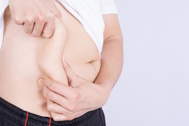 Homem gordo segurando a barriga gorda excessiva, fundo cinza com excesso de peso barriga gorda isolada. estilo de vida de dieta, perda de peso, músculo do estômago, conceito saudável.
