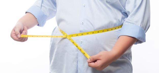 Homem gordo segurando uma fita métrica para verificar seu corpo isolado