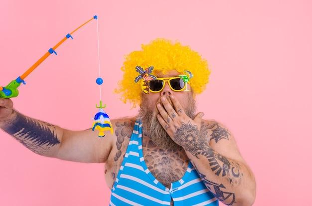 Homem gordo surpreso com barba e óculos escuros se divertindo com a vara de pescar