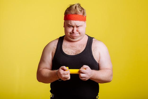 Homem gordo tenta levantar pequeno dumbell amarelo