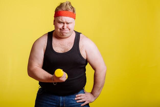 Homem gordo tentando levantar pequeno dumbell amarelo