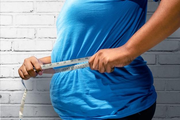 Homem gordo usando fita métrica para medir sua barriga