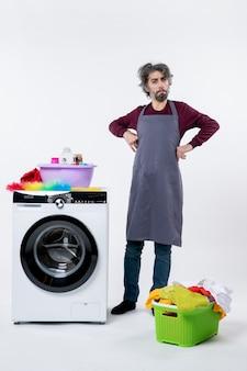 Homem governanta de vista frontal colocando as mãos na cintura em pé perto de uma máquina de lavar branca sobre fundo branco
