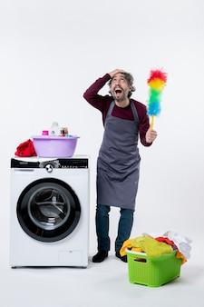 Homem governanta de vista frontal com espanador segurando a cabeça em pé perto do cesto de roupa suja da máquina de lavar no fundo branco