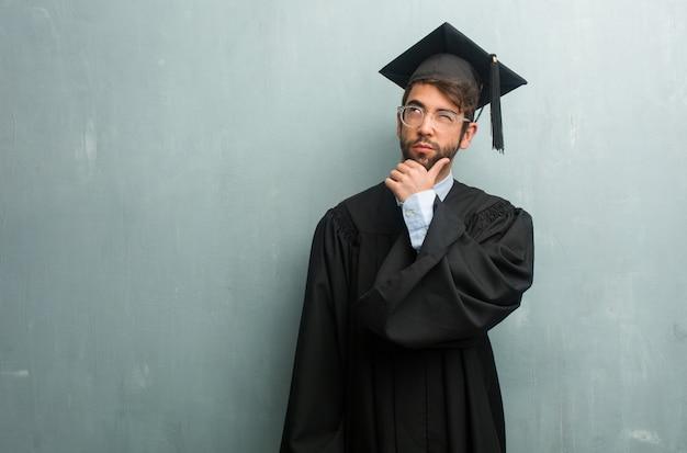 Homem graduado novo contra uma parede do grunge com um espaço da cópia que duvida e confuso