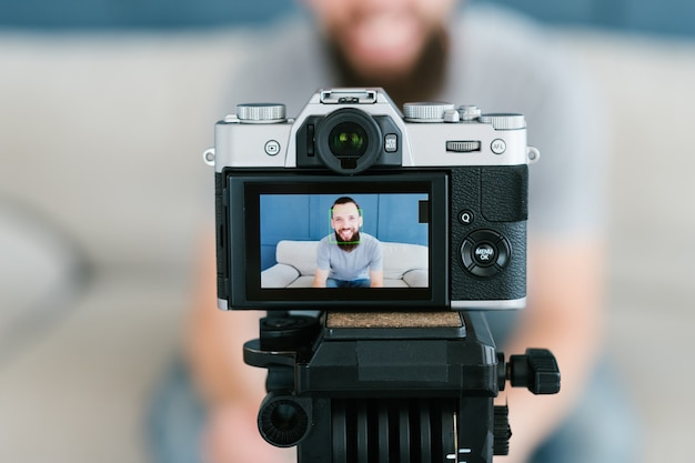 Homem gravando um vídeo de si mesmo usando a câmera no tripé. conceito moderno de tecnologia e equipamento.