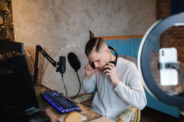 Homem gravando vídeo no smartphone durante o trabalho em casa no computador jovem gravando