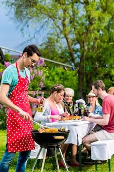 Homem grelhando carne em churrasco no jardim, ao fundo amigos comendo e bebendo