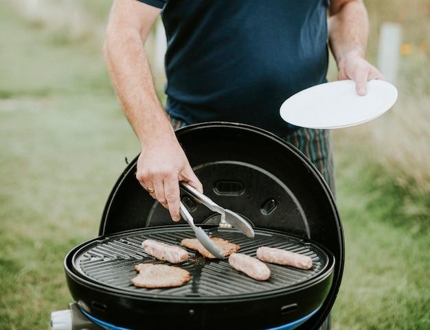 Homem, grelhando, carne, linguiças, ao ar livre