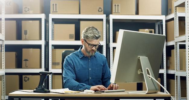 Homem grisalho caucasiano em copos trabalhando na tela do computador na loja de entrega postal e digitando no teclado.