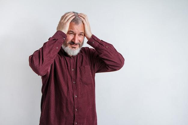 Homem grisalho com uma barba que sofre de dor de cabeça desesperada e estressada porque dor e enxaqueca