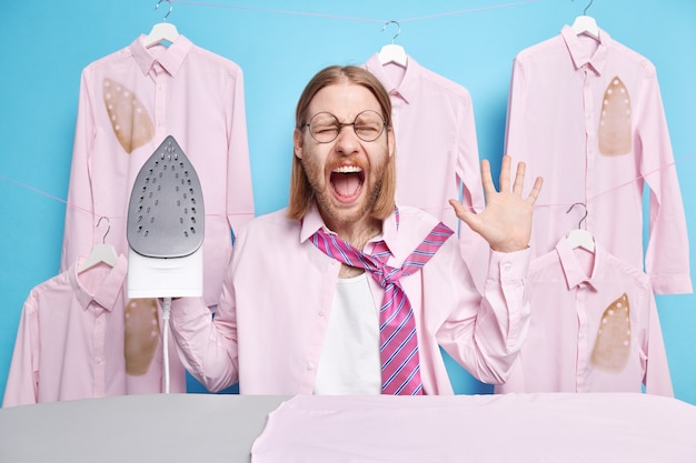 Homem grita alto mantém a boca aberta levanta palma segura ferro elétrico roupas pegue vestidos para reunião formal com colegas posa na lavanderia