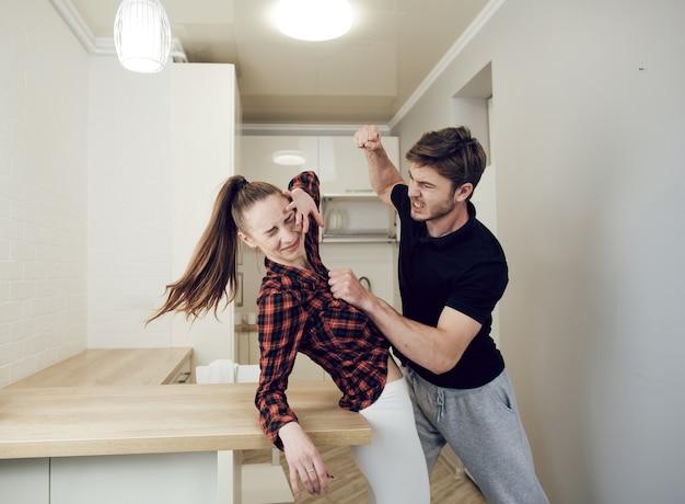 Homem grita com a mulher e ameaça com o punho. jovem assustada chorando.